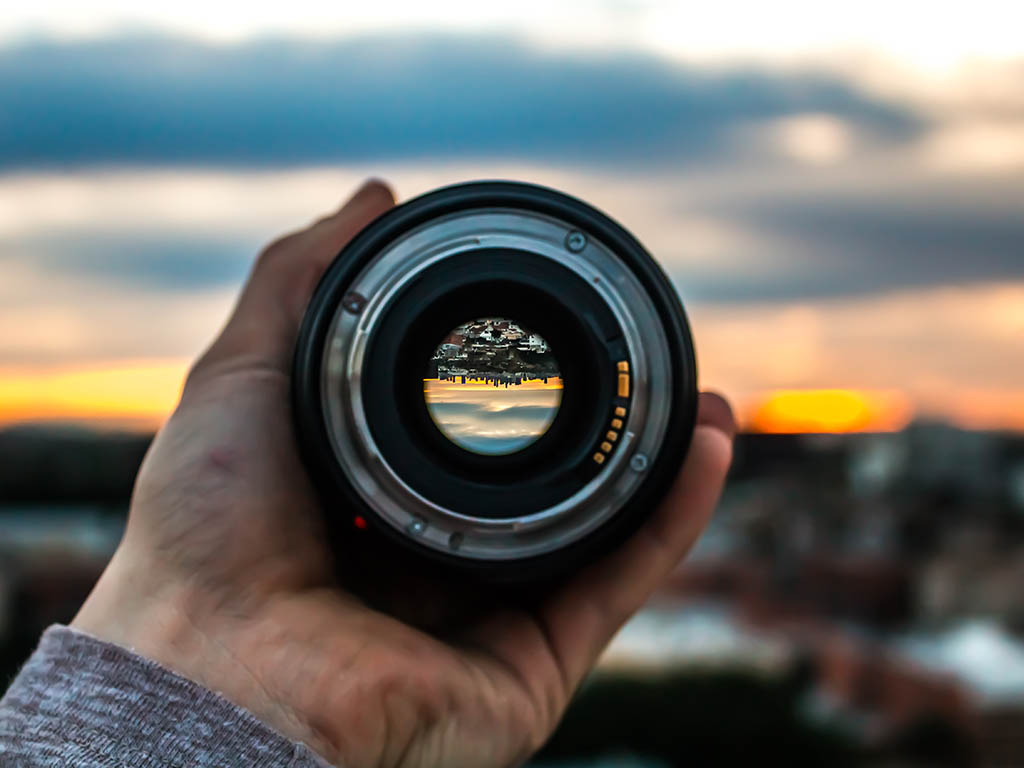 A person holding a camera lens up to a sunset