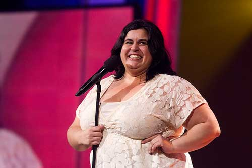 comedian Debra DiGiovanni laughs on stage