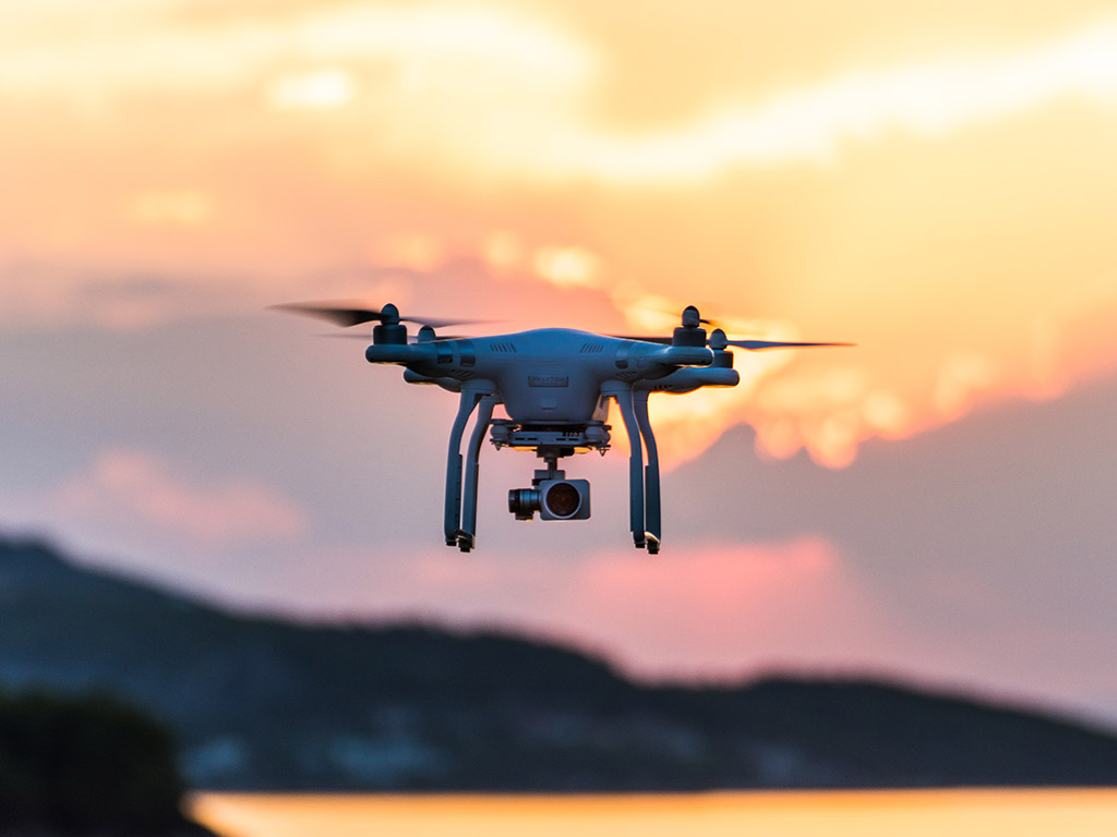A DJI drone in flight at sunset