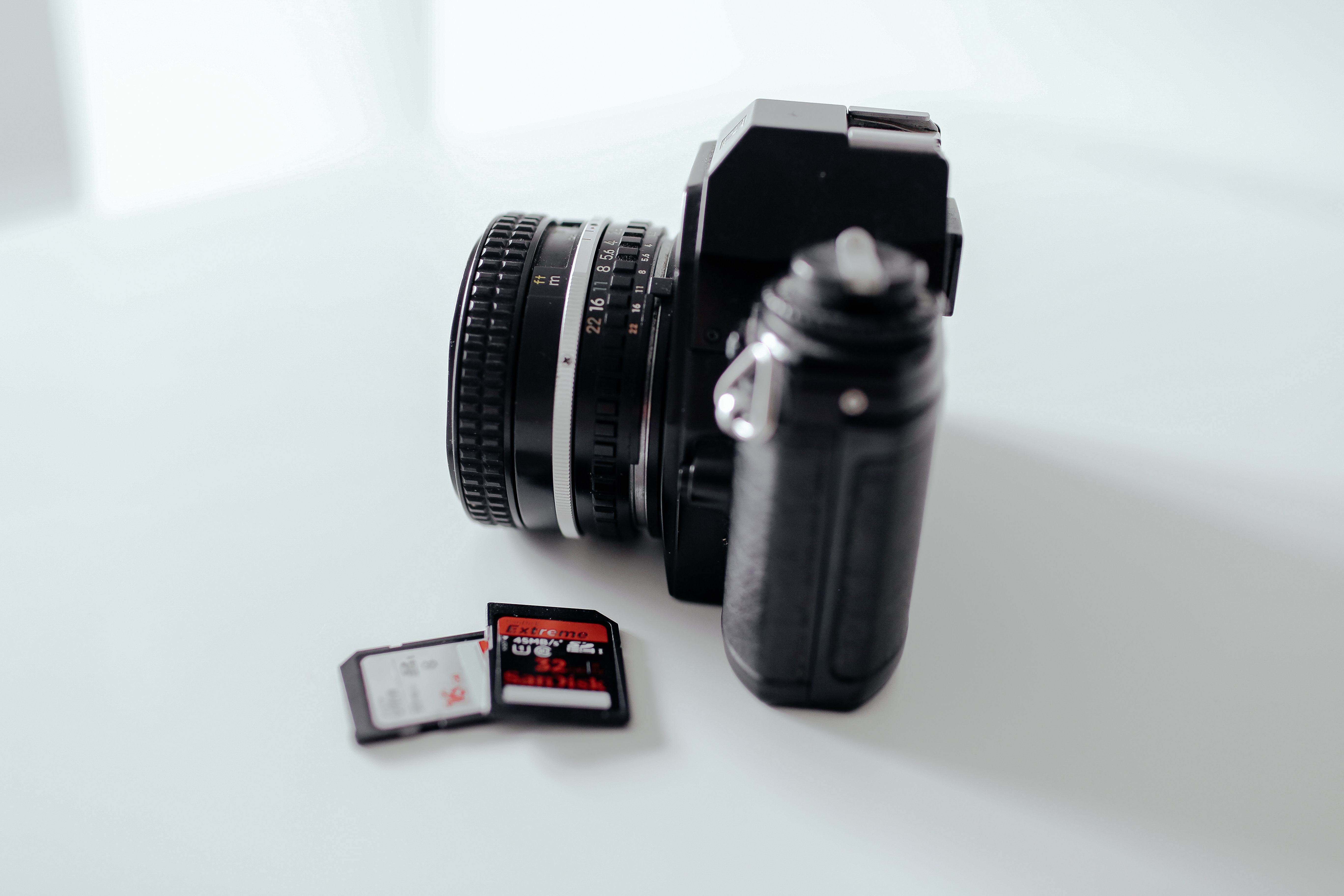 Photo of a camera with some SD cards sitting on a tabel