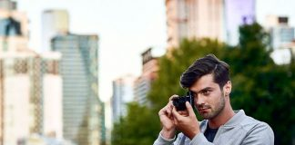 A photo of a photographer in an urban setting shooting with the Sony RX100 VI