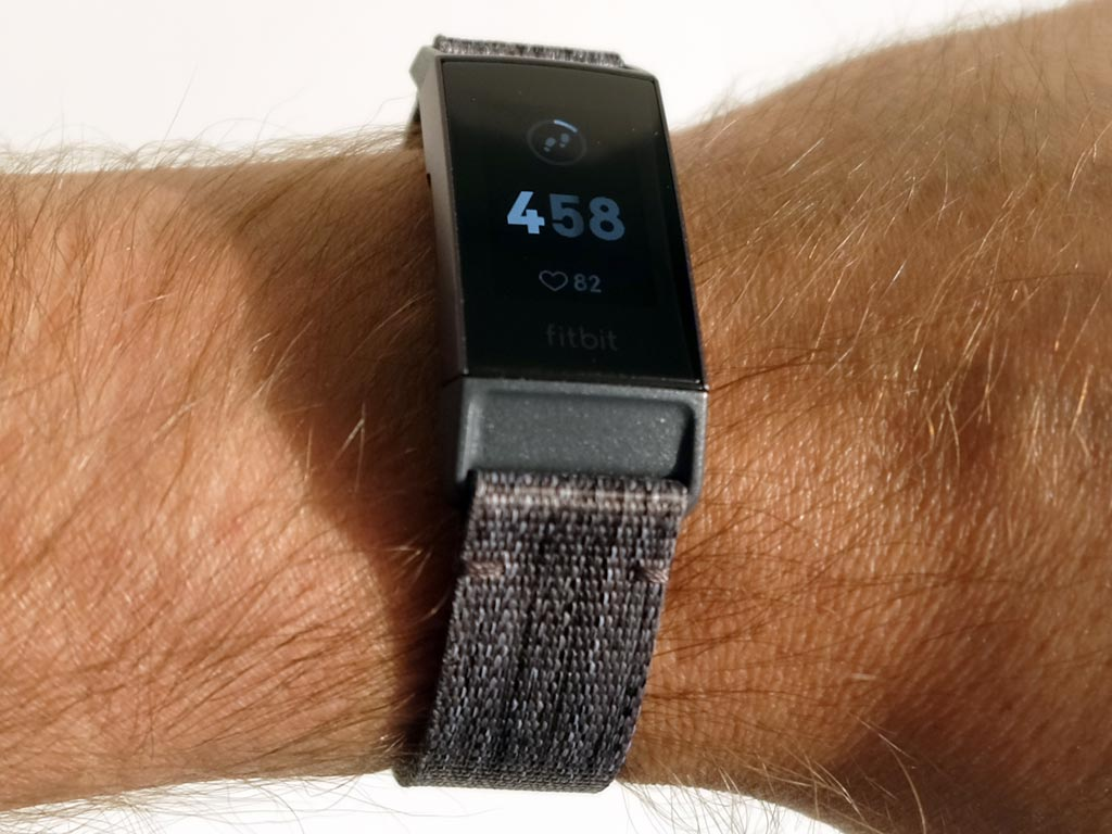 fitbit charge 3 strapped on a persons arm
