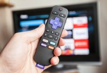 A photo of a hand holding a Roku remote control