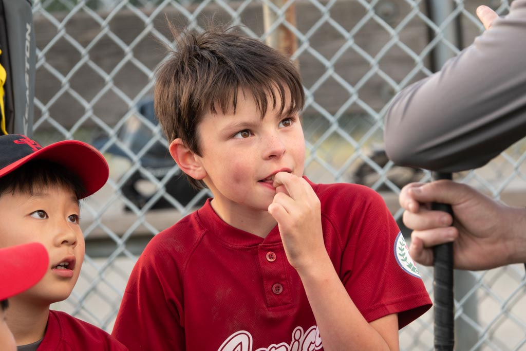 Photo of a boy in baseball uniform listening to his coach taken with the Sony RX10 IV