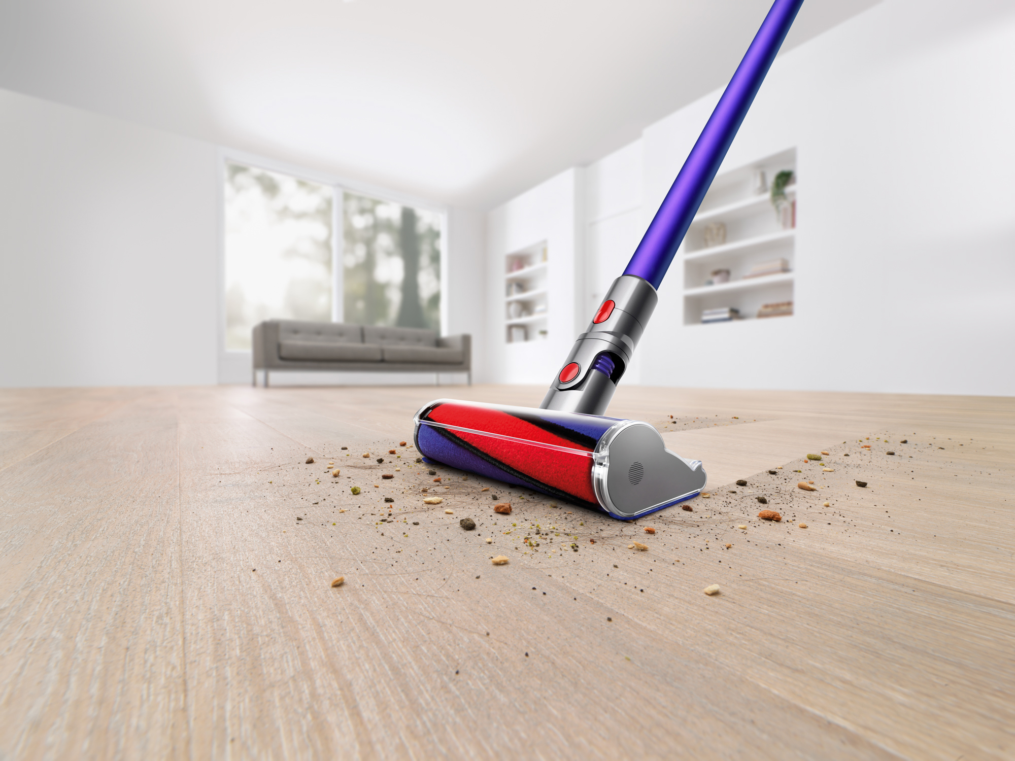The Dyson V11 Absolute Pro Cordless Stick Vacuum is shown cleaning a hardwood floor in a white room. It makes a clean sweep through the dust and debris on the floor, leaving nothing behind it.