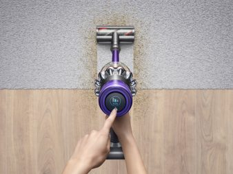 "A person vacuums from hardwood to carpet with the Dyson V11 Absolute Pro. They hold the vacuum in their right hand while their left hand points to to the LCD display which reads ""Auto."""