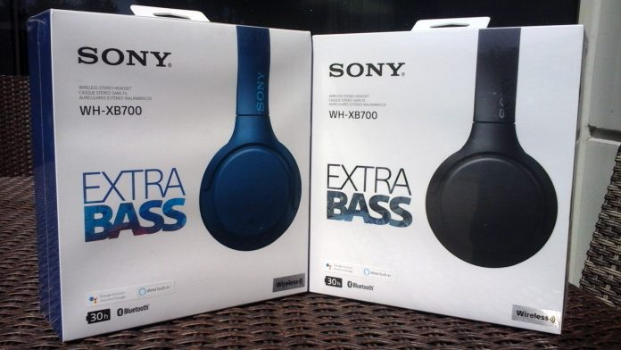 "Two white boxes containing Sony WH-XB700 headphones. Each is labeled ""SONY WH-XB700 EXTRA BASS."" The boxes are outdoors in the sunlight. The left box contains a pair of headphones in blue while the box on the right contains a pair of headphones in black."