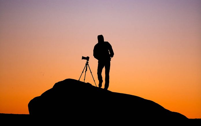 A photo of a photographer using a tripod to shoot a landscape