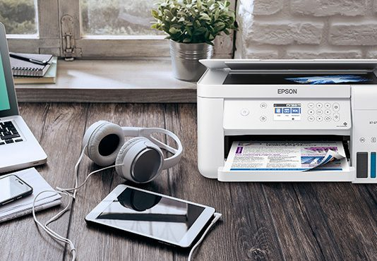 Printer on desk with headphones and notepad
