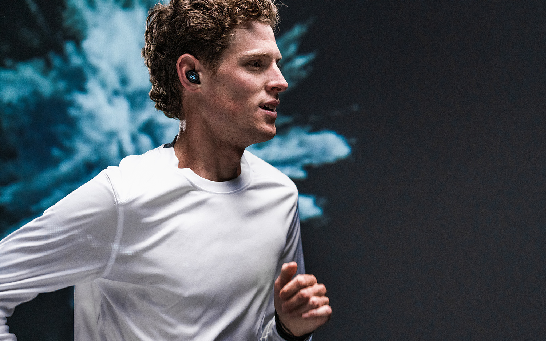 image of man running listening to music in Jaybird Vista truly wireless headphones