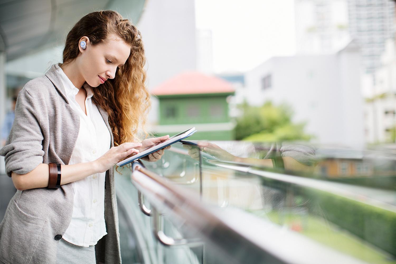 image of woman outside wearing JBL truly wireless headphones