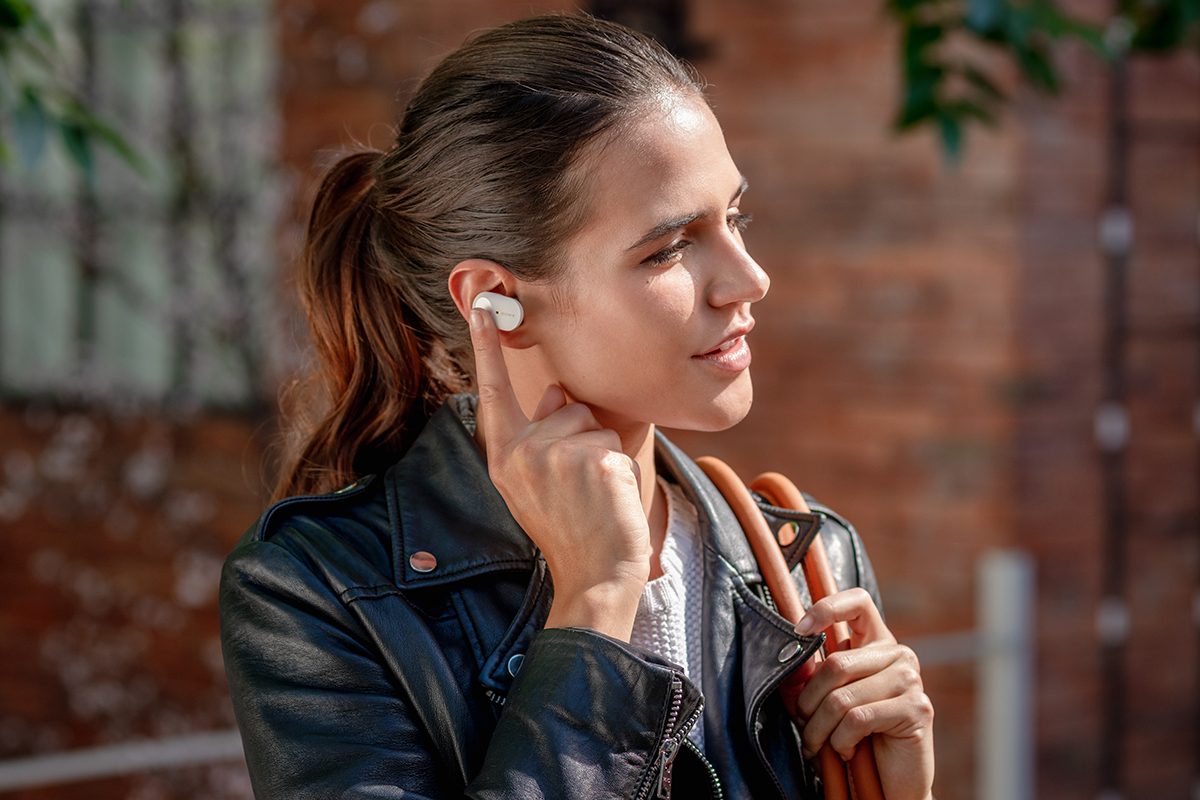 image of woman taking a phone call with the Sony 1000XM3 headphones