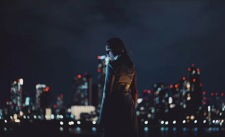 A photo of a woman and a city skyline at night. Provided by Sony