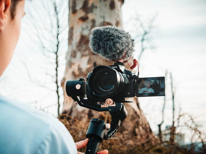 A man is filming himself with a camera mounted on a gimbal