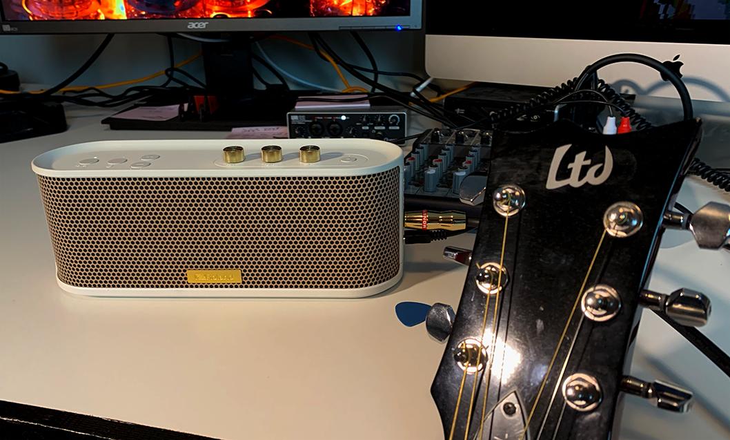 ROland BTM-1 bluetooth speaker next to a leaning guitar