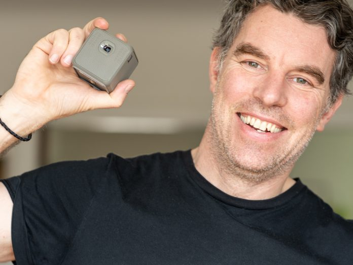 A photo of photographer Justin Morrison holding the XPRIT smart cube projector