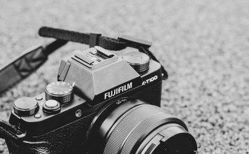 A photo of a mirrorless camera sitting on the ground