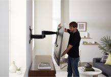 image of man adjusting a mounted TV