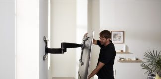 image of man adjusting a mounted TV