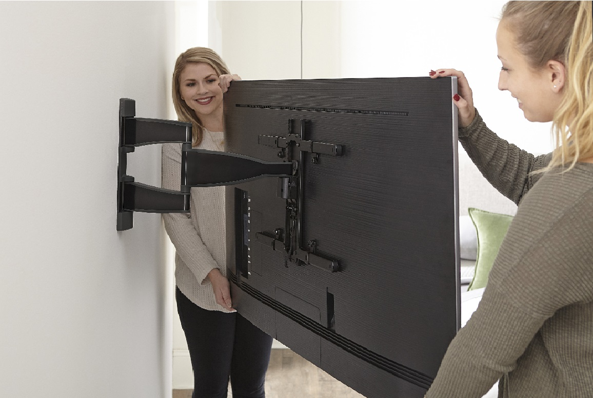 image of two women mounting a TV