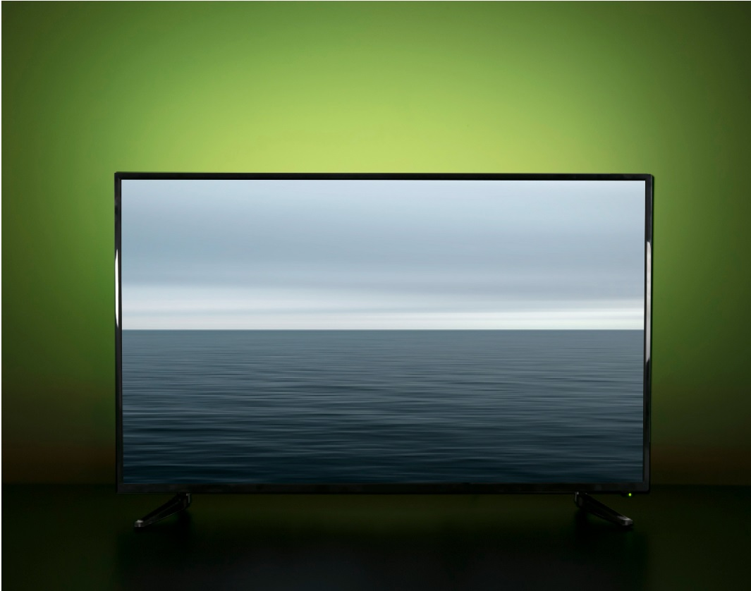 image of a TV with LED strip lights shining a green glow from the wall behind it