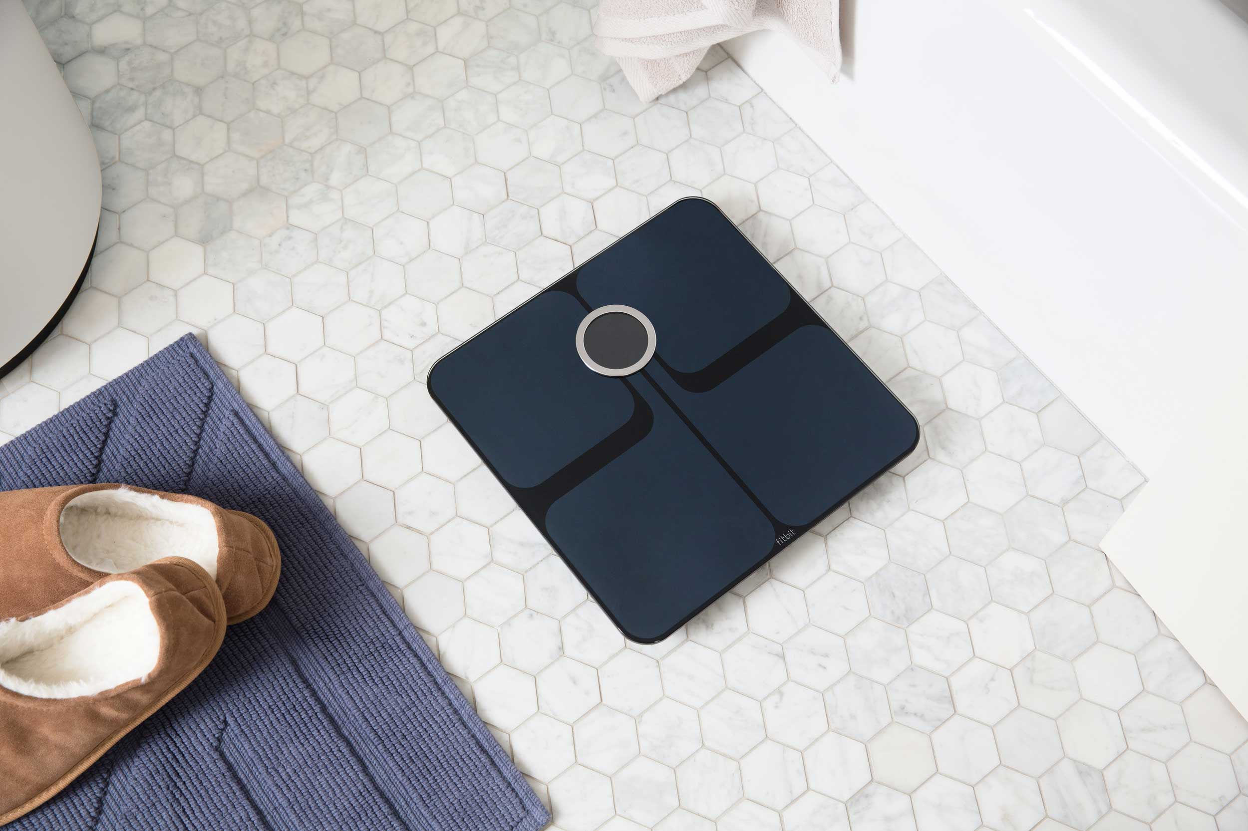 Lifestyle photo of a dark coloured fitbit smart scale on the bathroom floor