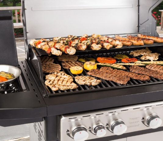 image of an open BBQ with the grill covered in cooking steaks, sausages, veggies, chicken, and skewers