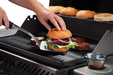 image of a person cooking burgers on a BBQ while burger buns are warmed on the warming rack