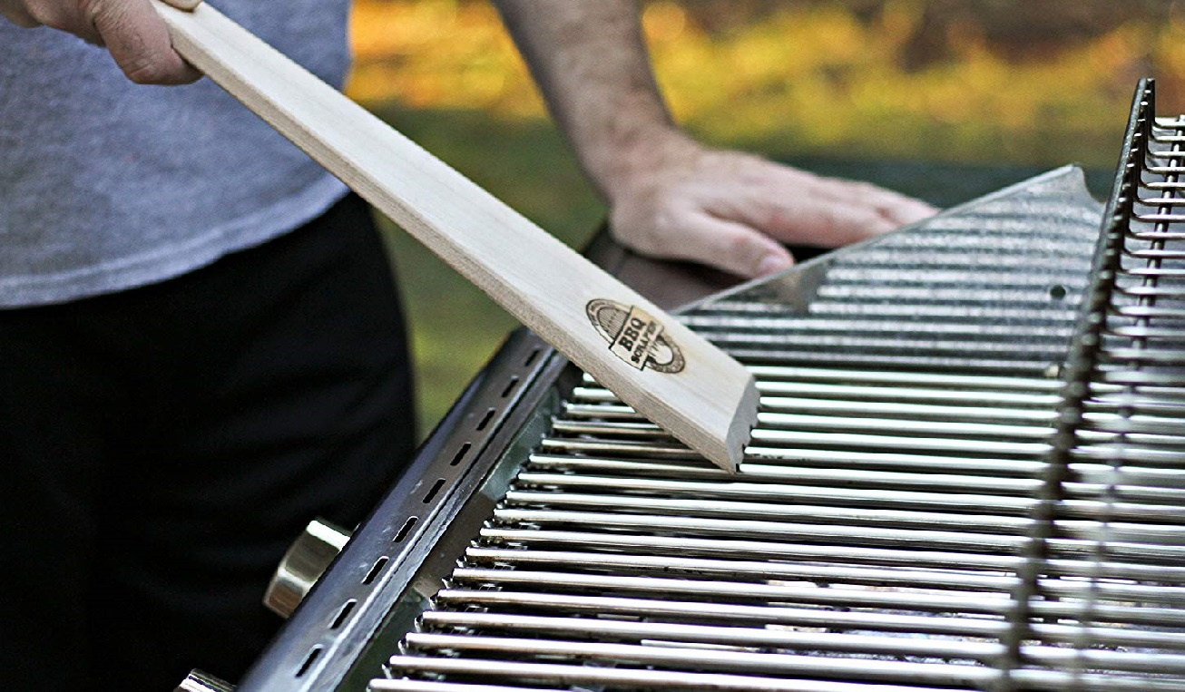 image of a person using a wooden BBQ scraper to clean a BBQ grate