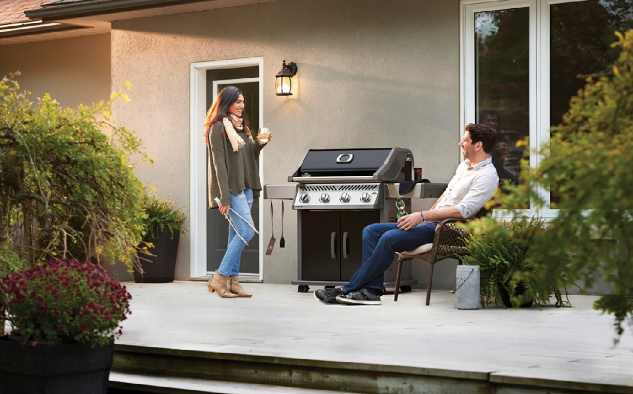 image of two people in conversation on their patio next to their BBQ