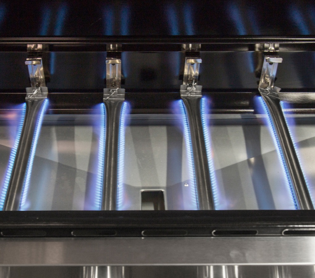 image of 4 burners in a BBQ alight with flames