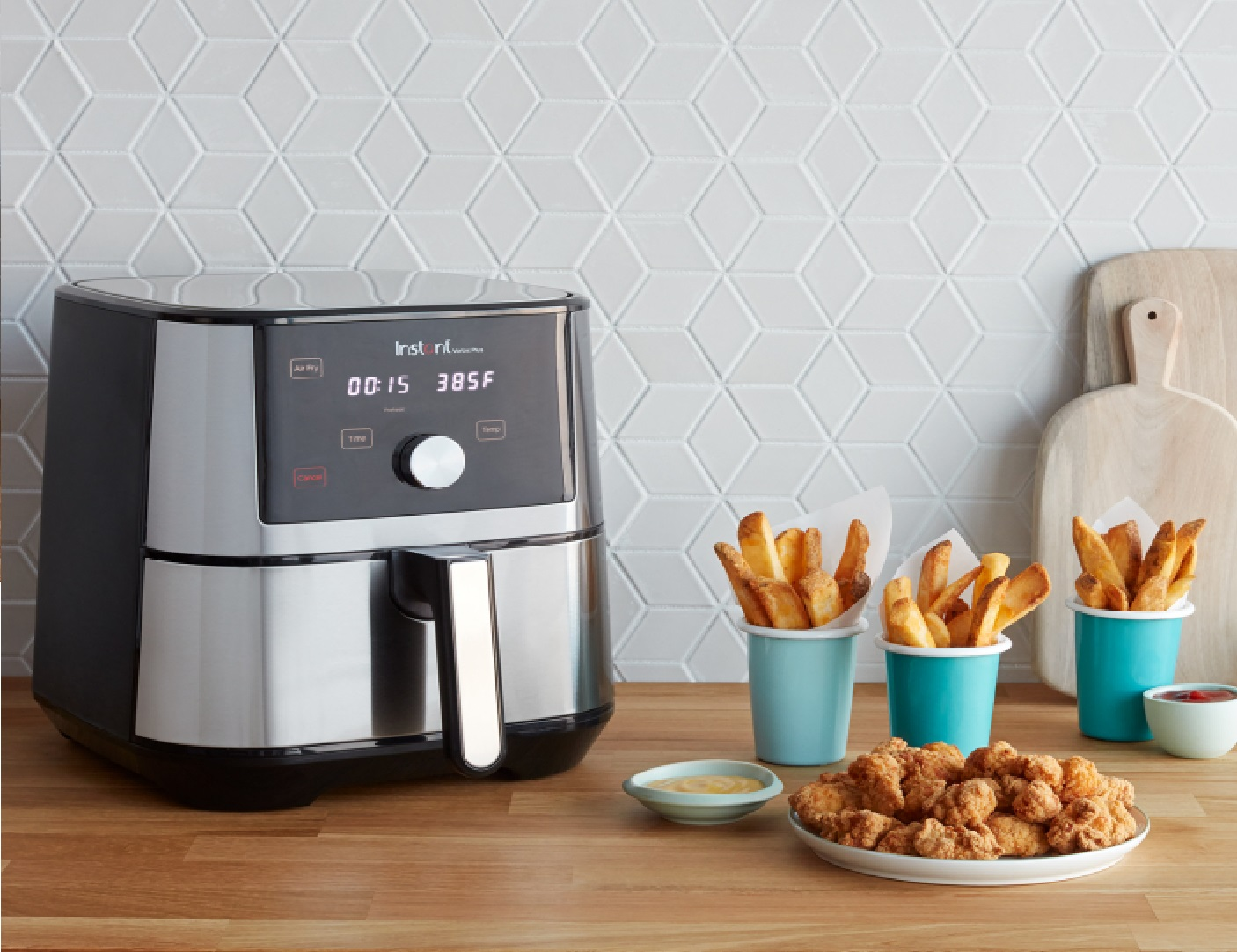 image of the Instant Pot Vortex Plus Air Fryer Oven on a table surrounded by tasty treats