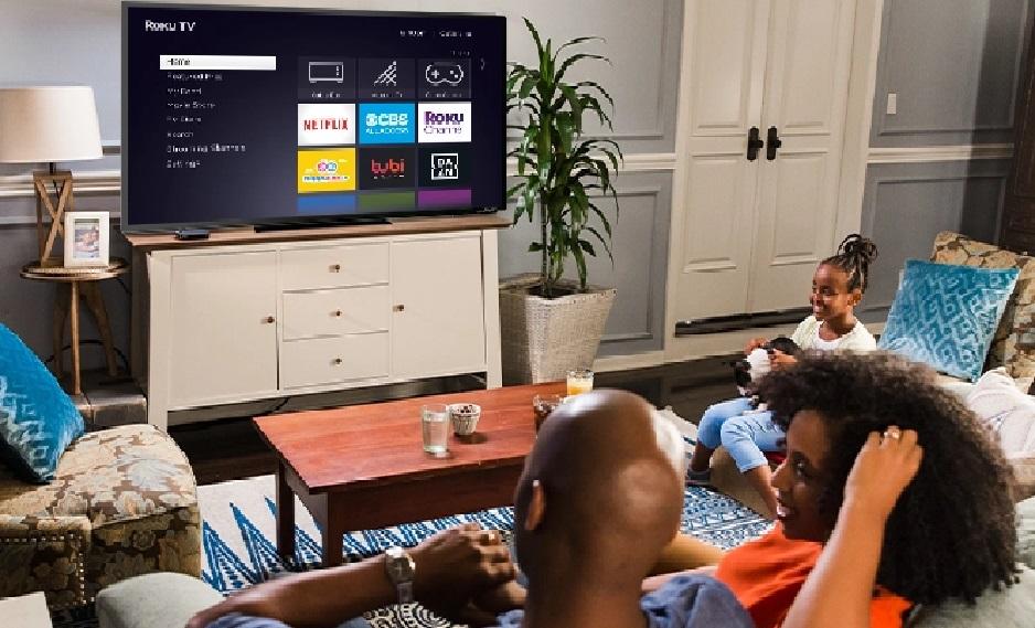 image of a family watching a Roku Smart TV displaying the Roku menu