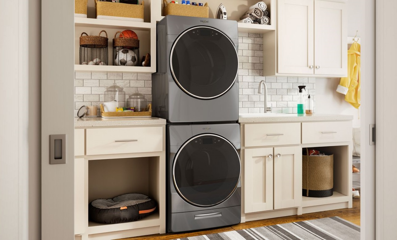 Image of a stacked Whirlpool laundry pair among many storage cabinets
