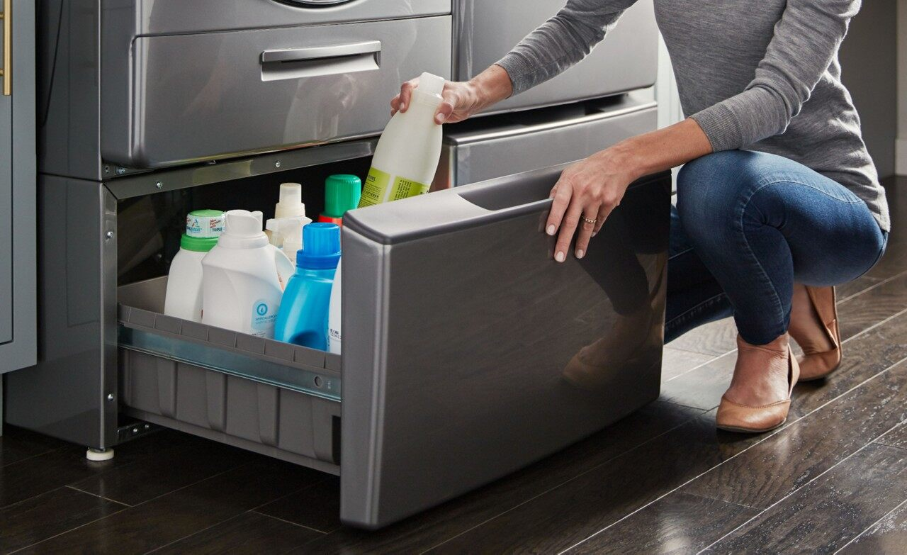 Image of a woman opening a pedestal drawer beneath a washing machine to store cleaning supplies