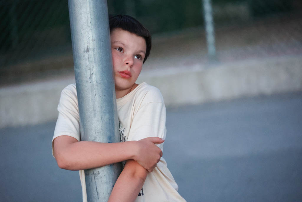 A photo of a boy by a basketball hoop