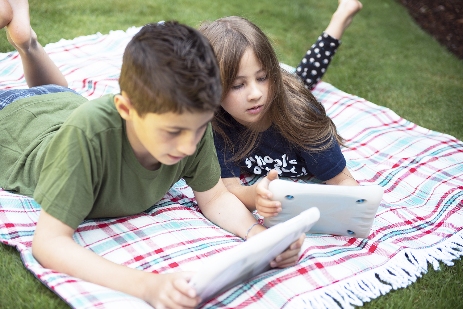 image showing two children on a blanket looking at tablets