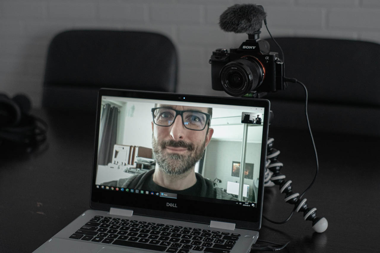 A photo of a laptop and a man using a Sony camera as a webcam