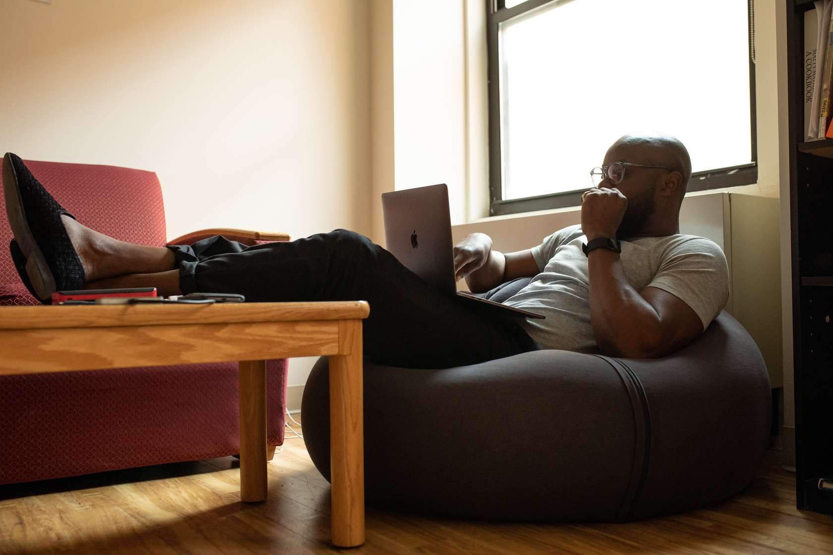 image of a man working on a laptop on a bean bag chair