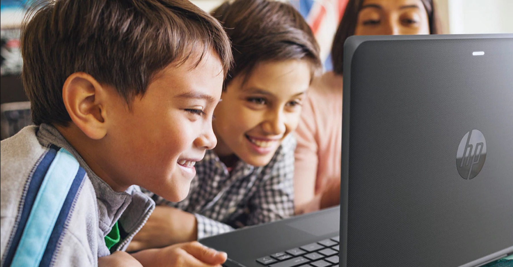 image of 2 boys looking at a laptop screen