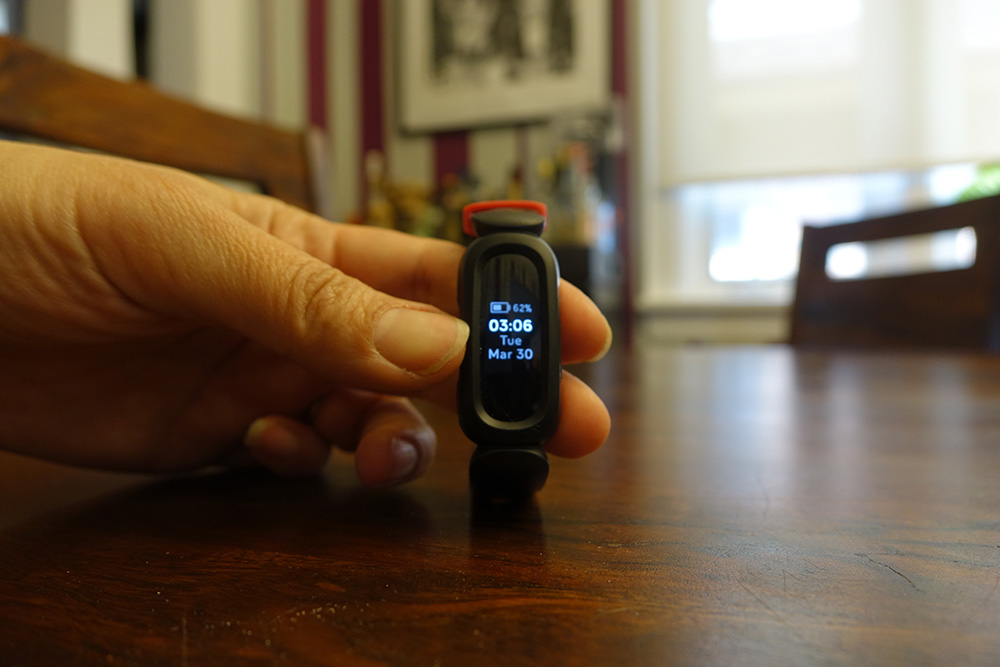 Fitbit Ace 3 upright on table showing date and time