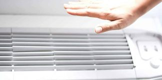 image of a hand feeling cool air from an air conditioner