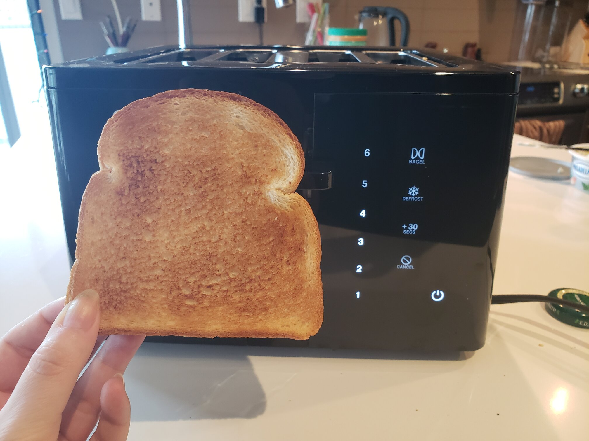 image of a perfectly toasted slice of bread next to the toaster