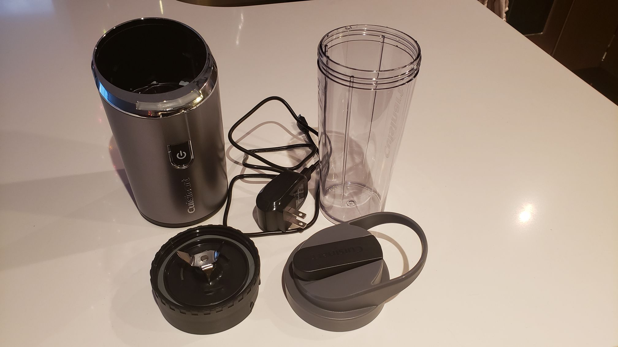 image of all the blender components: base, blades, tumbler, travel lid, and cord