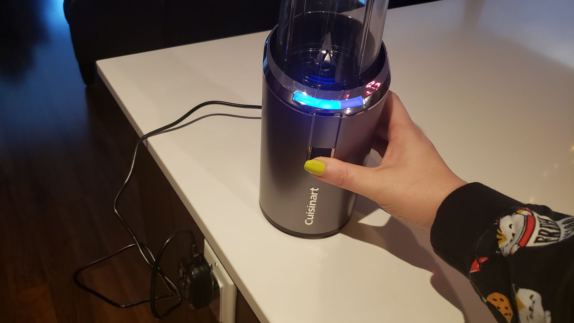 image of a hand pressing the blend button while the blender is plugged in