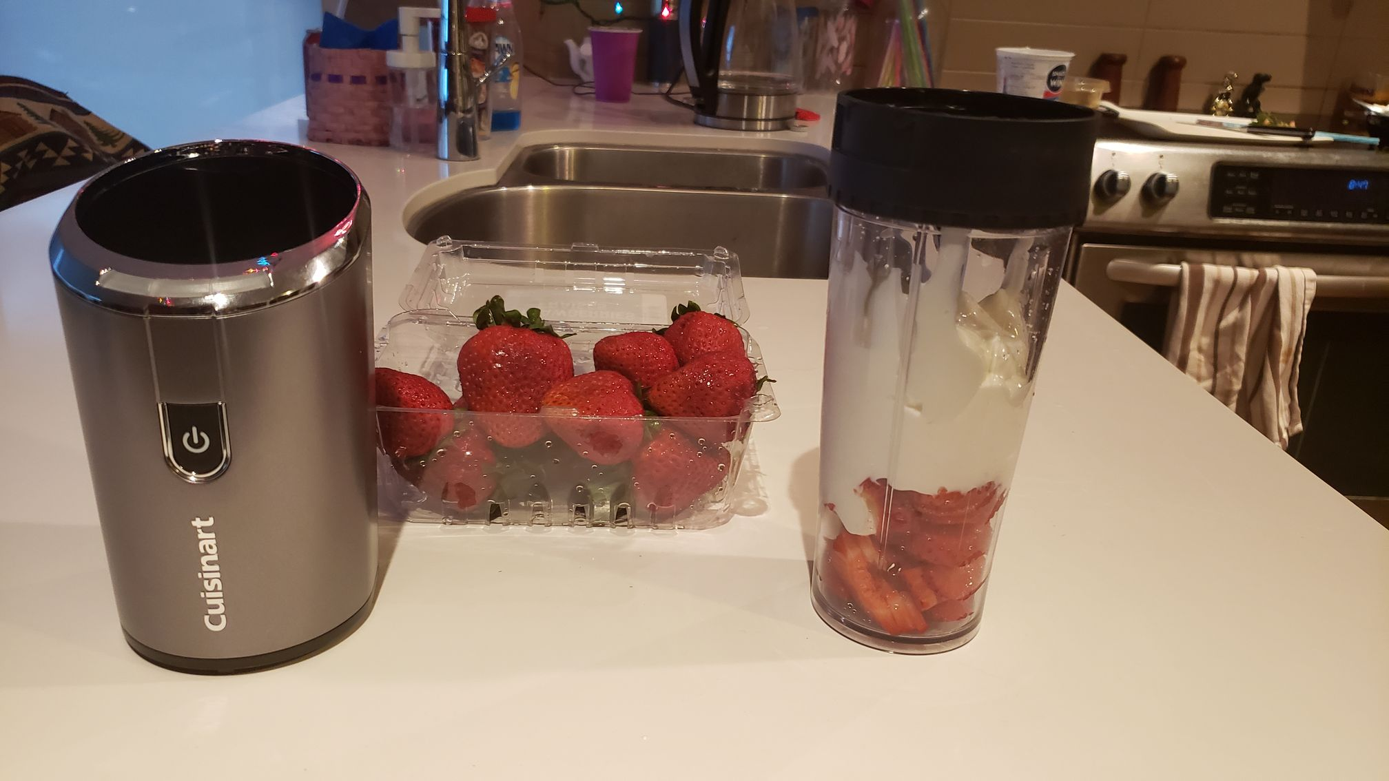 image of blender base next to fresh strawberries and tumbler full of ingredients