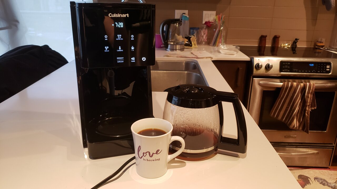 image of the coffee maker next to the carafe and mug of coffee