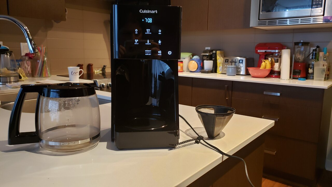 image of the coffee maker next to the carafe and reusable filter