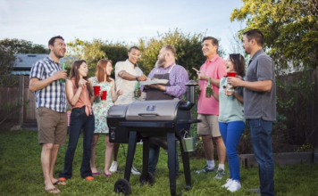 group of friends gathered around a smoker.
