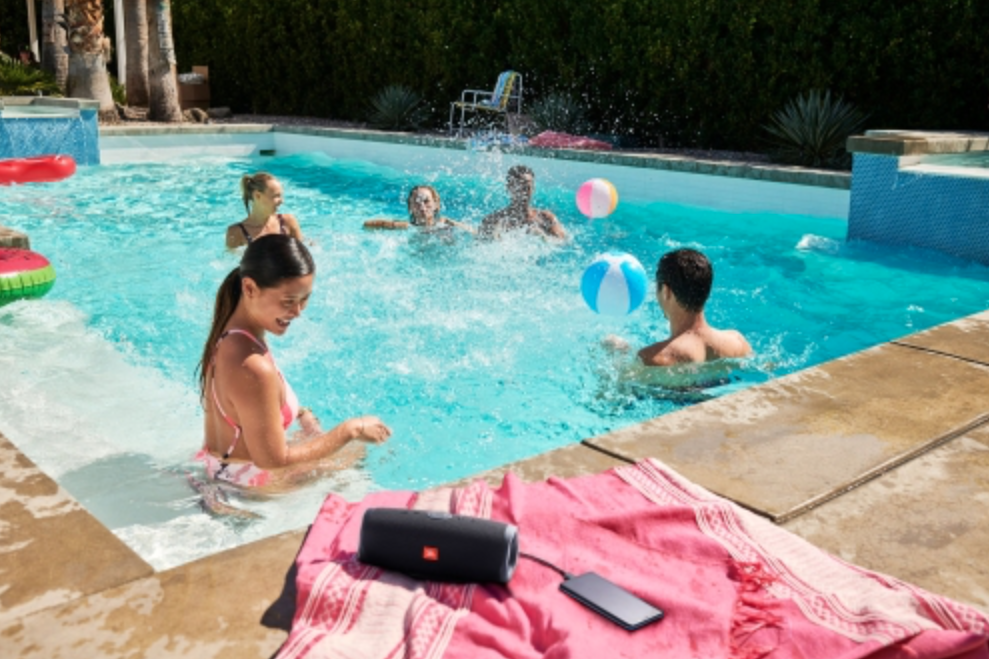 friends hanging at the pool with a JBL portable Bluetooth speaker on the side.